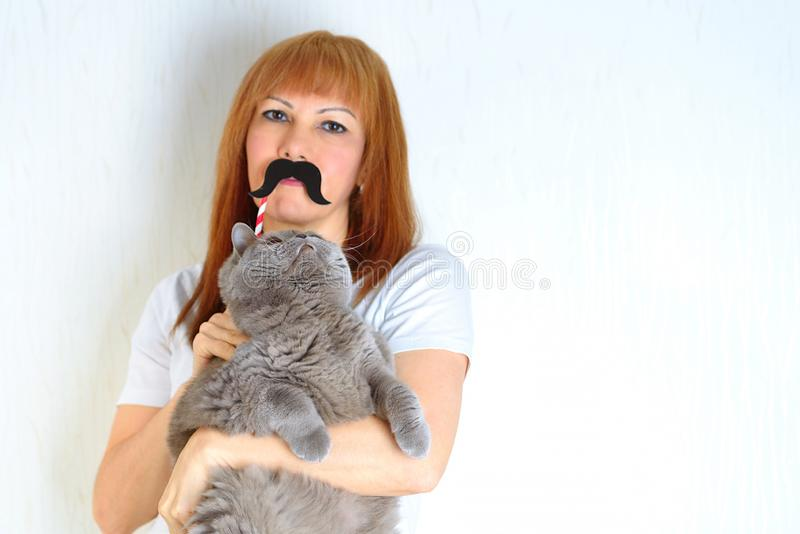 Rijpe vrouw die pret met een valse snor hebben en huisdier omhelzen royalty-vrije stock afbeeldingen