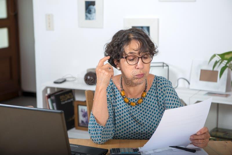 Rijpe vrouw die rekeningen betalen en een probleem hebben stock foto