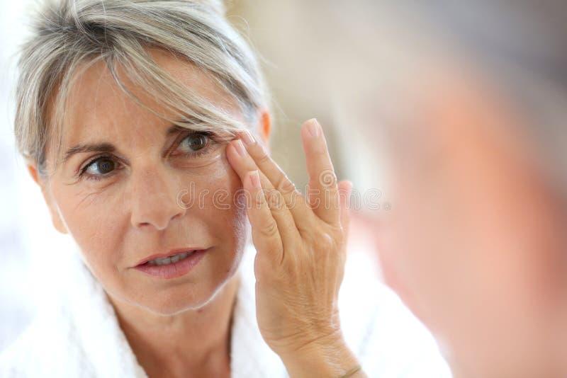 Rijpe vrouw die room op gezicht toepassen royalty-vrije stock afbeelding