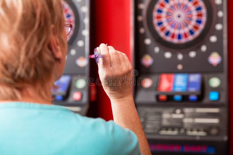 Rijpe vrouw die tegen dartboard streven royalty-vrije stock foto