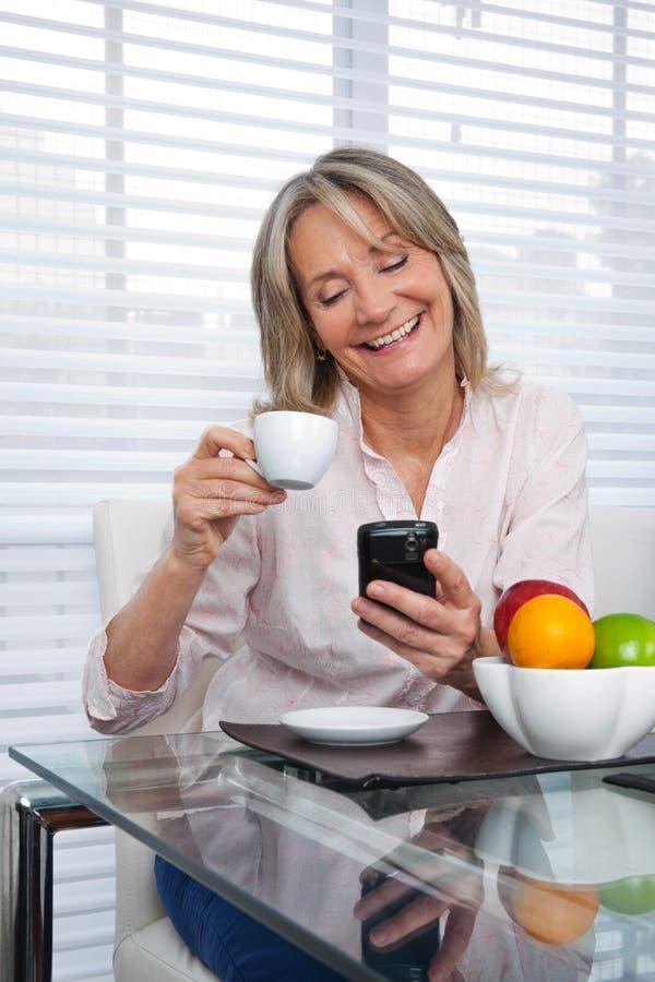 Rijpe Vrouw die Telefoon met behulp van stock afbeelding