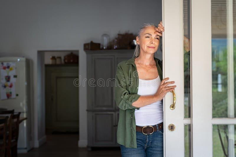 Rijpe vrouw die thuis ingang denken stock afbeelding