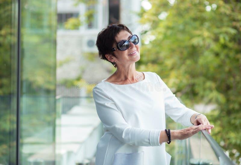Rijpe vrouw die upwards dagdromen kijken royalty-vrije stock afbeeldingen