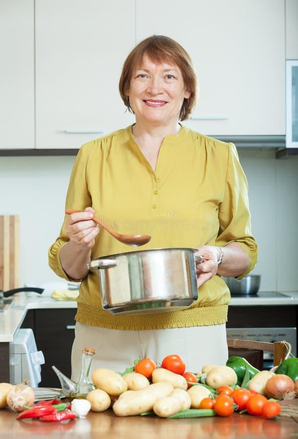 Rijpe vrouw die vegetarische lunch koken royalty-vrije stock afbeeldingen