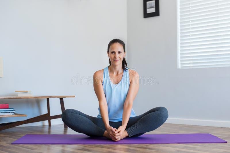 Rijpe vrouw die yoga doet stock afbeelding