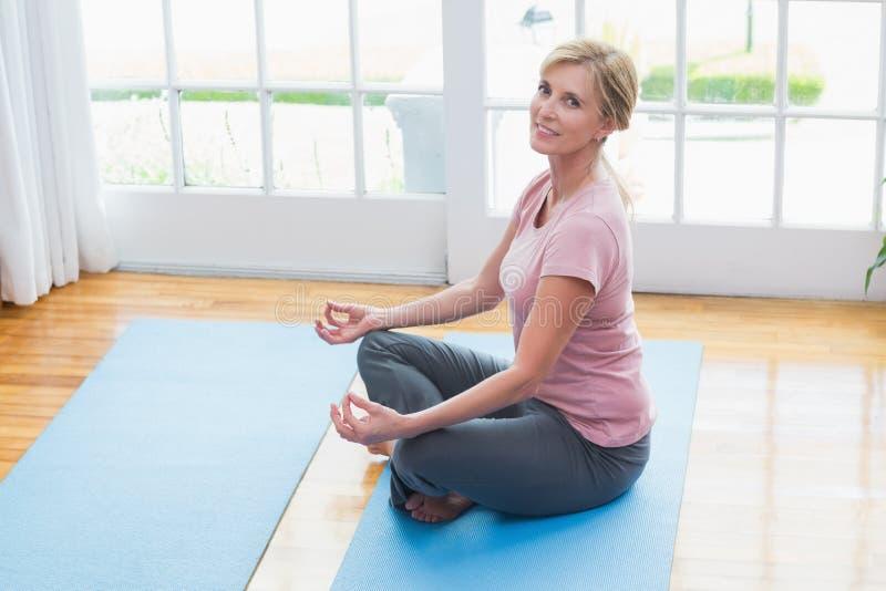 Rijpe vrouw die yoga op geschiktheidsmat doen stock afbeeldingen