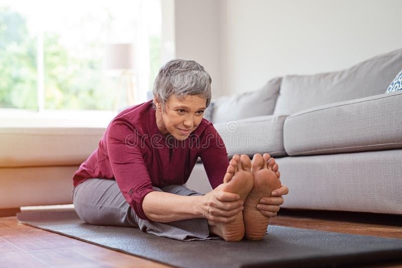 Rijpe vrouw die yogaoefening thuis doen royalty-vrije stock foto