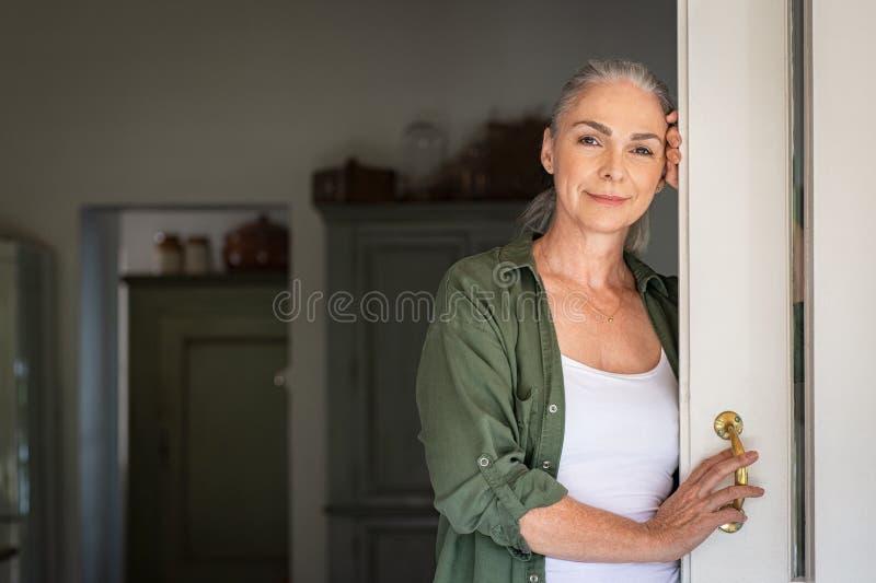 Rijpe vrouw die zich bij deur bevinden stock fotografie