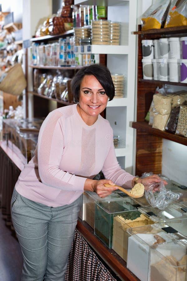 Rijpe vrouw die zich naast containers met kruiden bevinden royalty-vrije stock fotografie