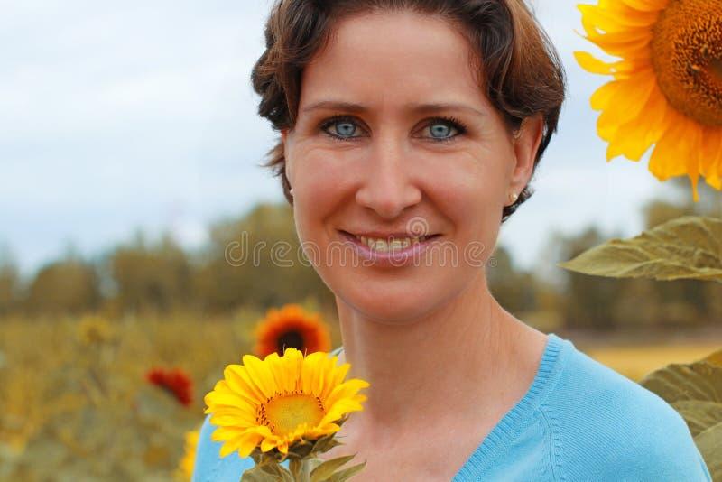 Rijpe vrouw die zich op een zonnebloemgebied bevinden stock foto's