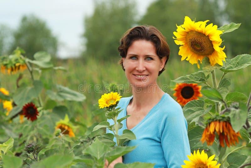 Rijpe vrouw die zich op een zonnebloemgebied bevinden royalty-vrije stock fotografie