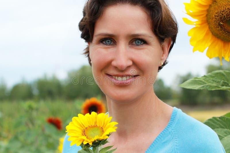 Rijpe vrouw die zich op een zonnebloemgebied bevinden stock afbeelding