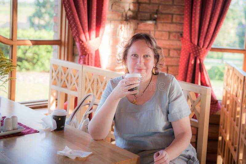 Rijpe vrouw in een koffie stock foto