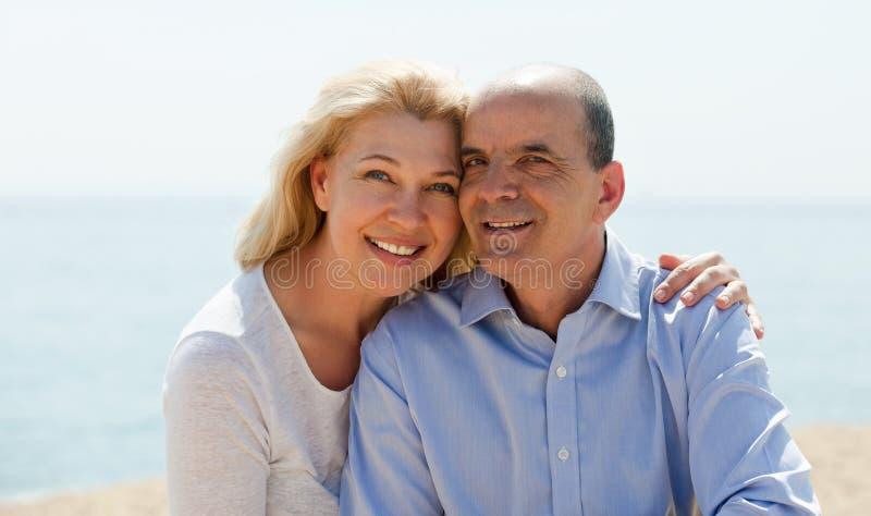 Rijpe vrouw en hoger op zee strand bij vakantie het glimlachen stock foto