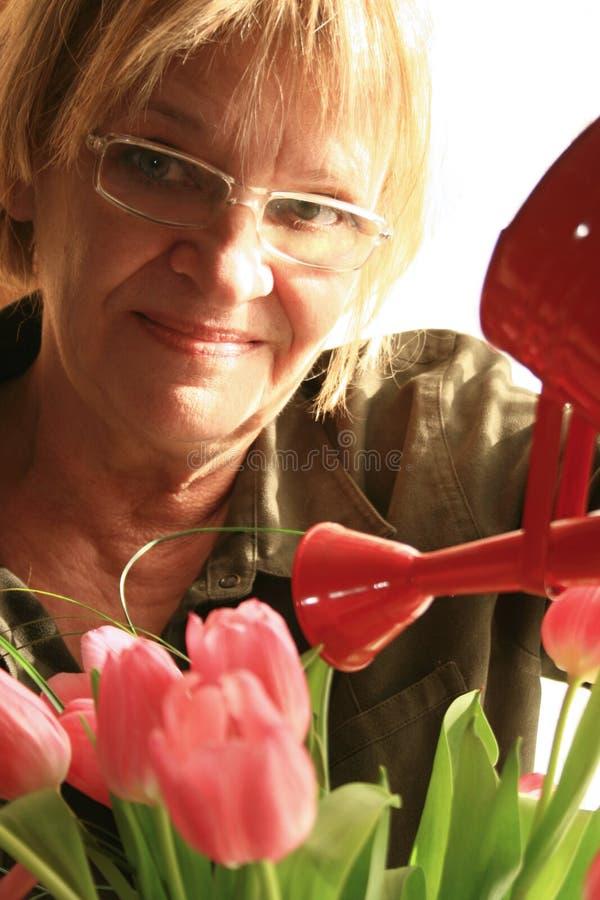 Rijpe vrouw en tulpen stock afbeelding