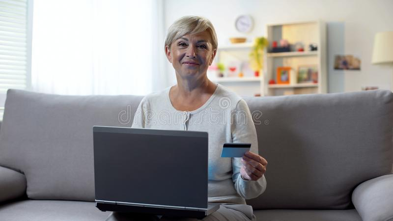 Rijpe vrouw gebruikend laptop, houdend creditcard en glimlachend bij camera, het beleggen royalty-vrije stock afbeelding