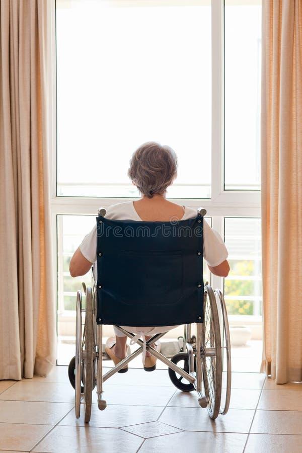 Rijpe vrouw in haar rolstoel stock afbeelding