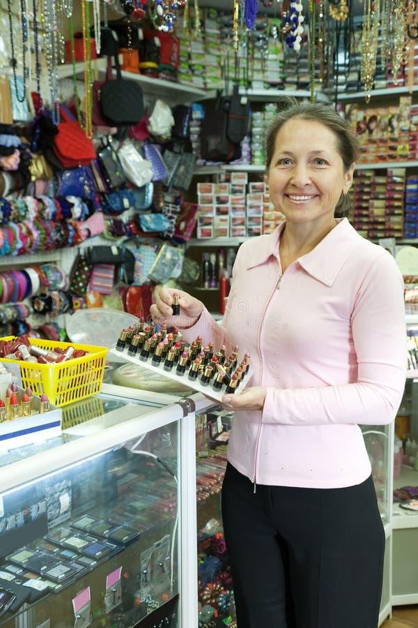 Rijpe vrouw het kopen lippenstift stock afbeelding
