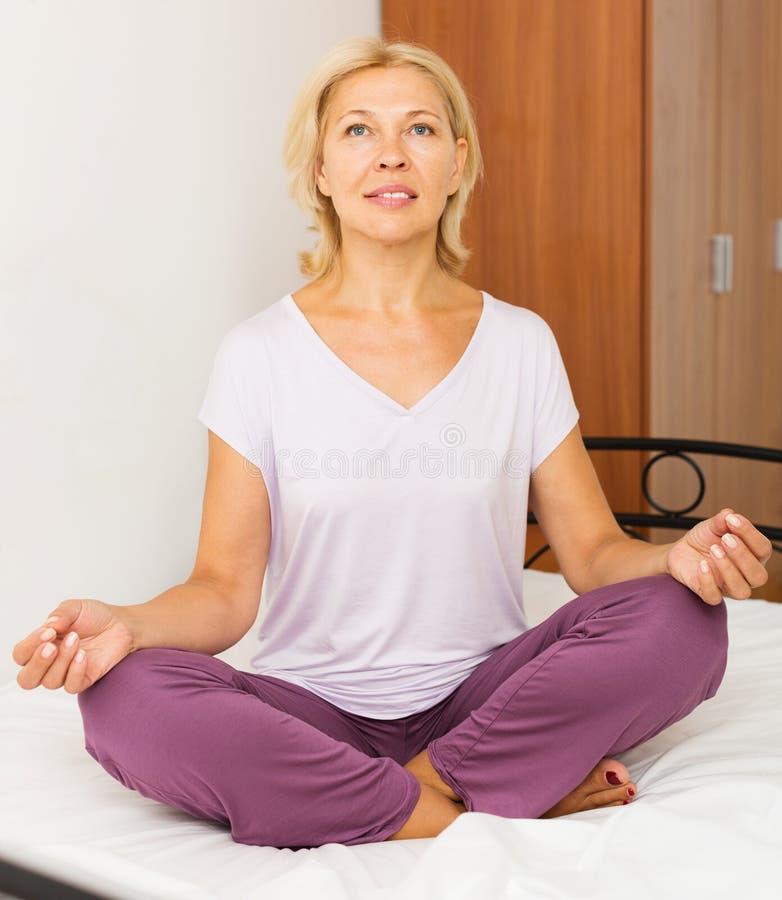 Rijpe vrouw het praktizeren yoga stock afbeelding
