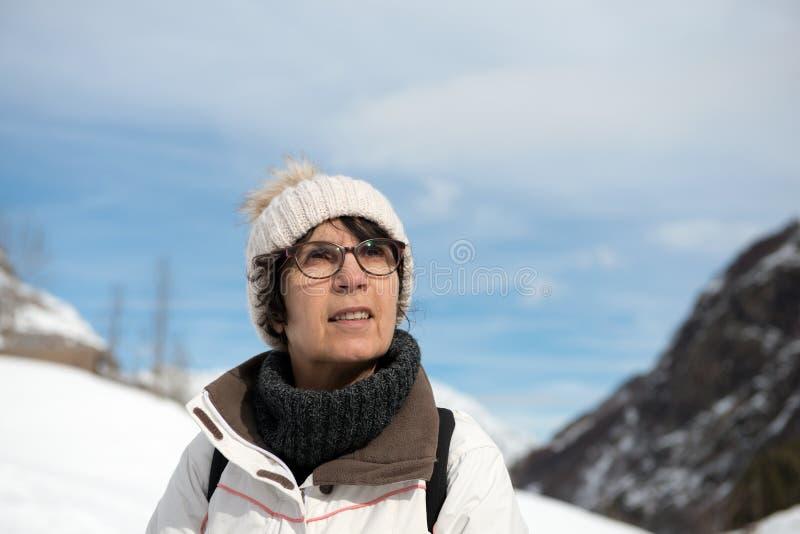 Rijpe vrouw met de winter GLB in de berg stock afbeelding