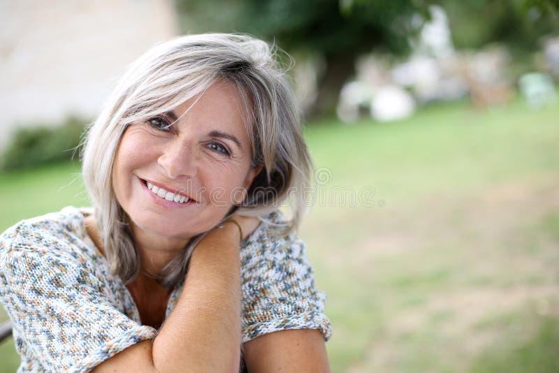 Rijpe vrouw met een stille blikzitting in tuin royalty-vrije stock fotografie