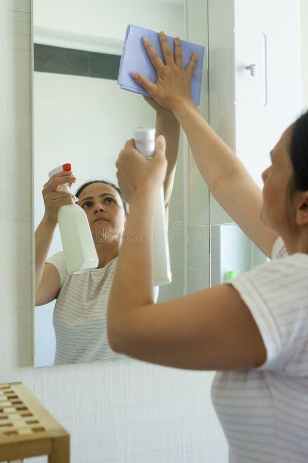 Rijpe vrouw met het schoonmaken van nevel en doek in badkamers stock foto