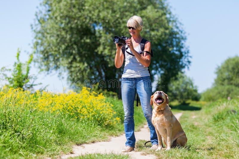 Rijpe vrouw met hond die foto's met een camera nemen stock afbeeldingen
