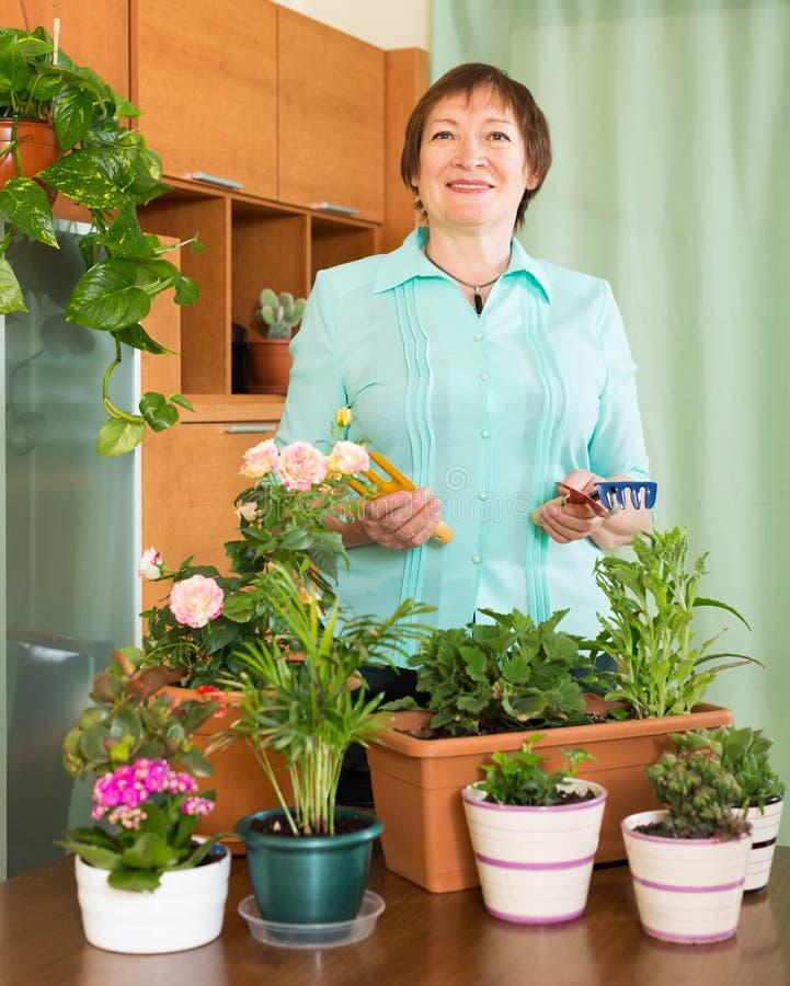 Rijpe vrouw met installaties thuis stock foto