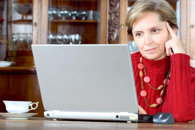 Rijpe vrouw met laptop stock afbeelding