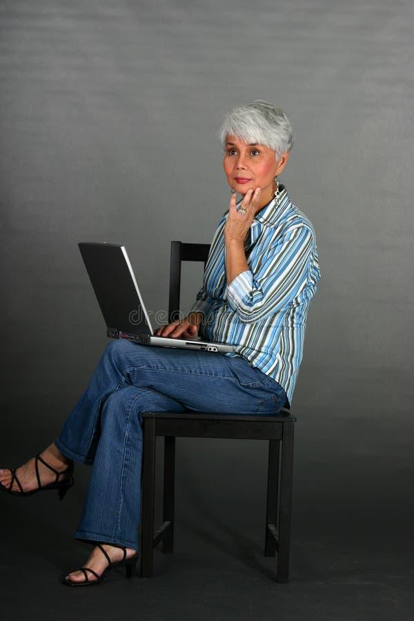 Rijpe vrouw met laptop stock afbeeldingen