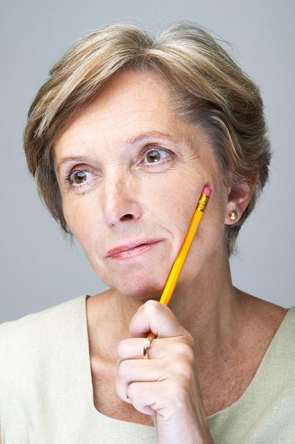 Rijpe vrouw met potlood stock afbeeldingen