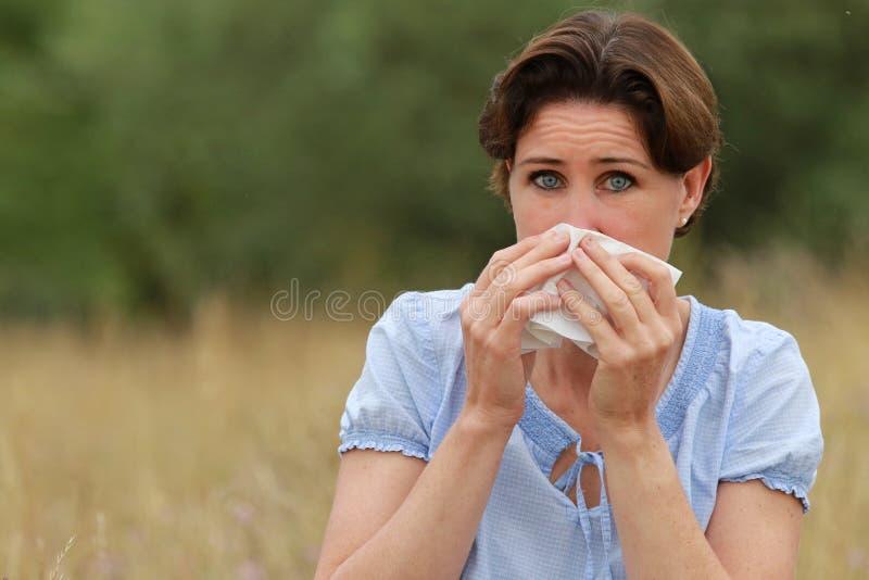 Rijpe vrouw met zakdoek die haar neus blazen stock afbeeldingen