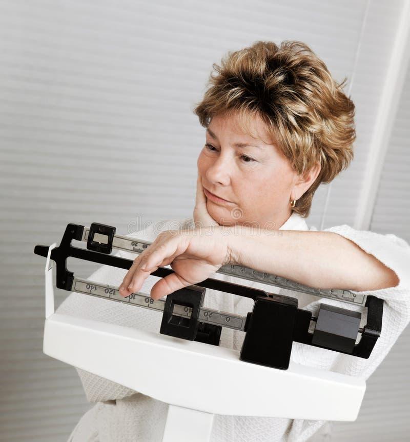 Rijpe Vrouw op de Schaal van het Gewicht stock foto