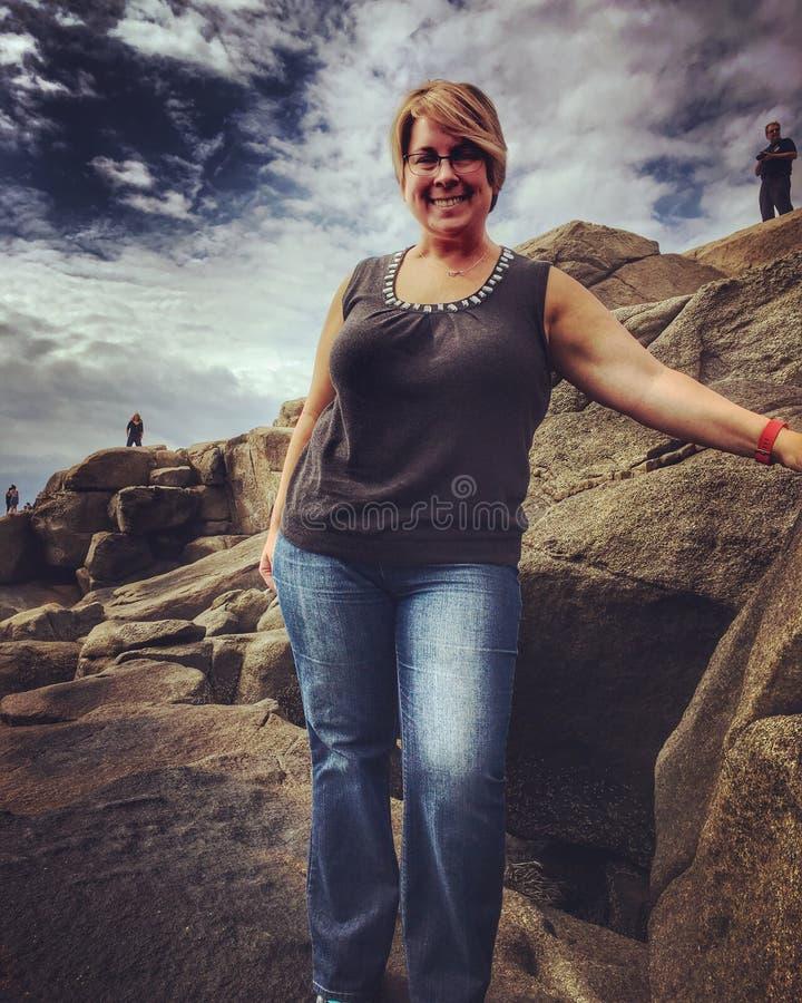 Rijpe vrouw op rotsen royalty-vrije stock foto's