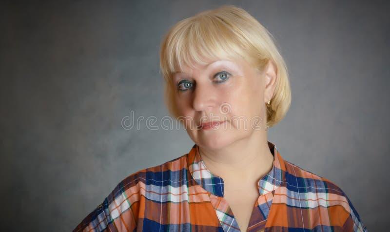 Rijpe vrouw op zwarte stock fotografie