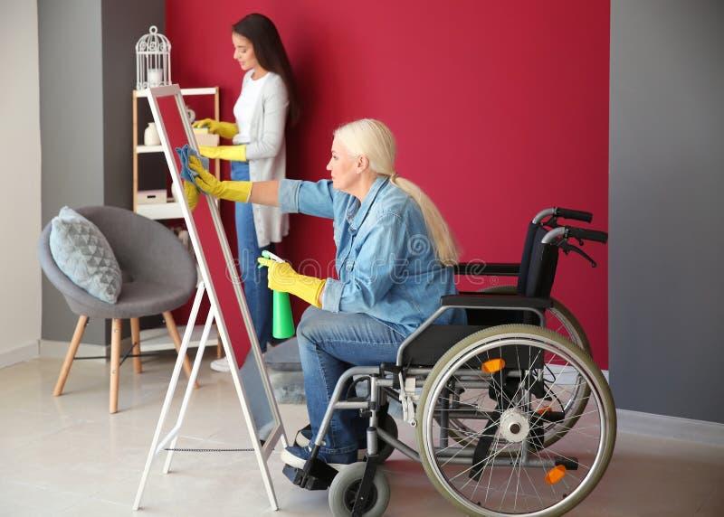 Rijpe vrouw in rolstoel en haar dochter schoonmakend huis stock foto