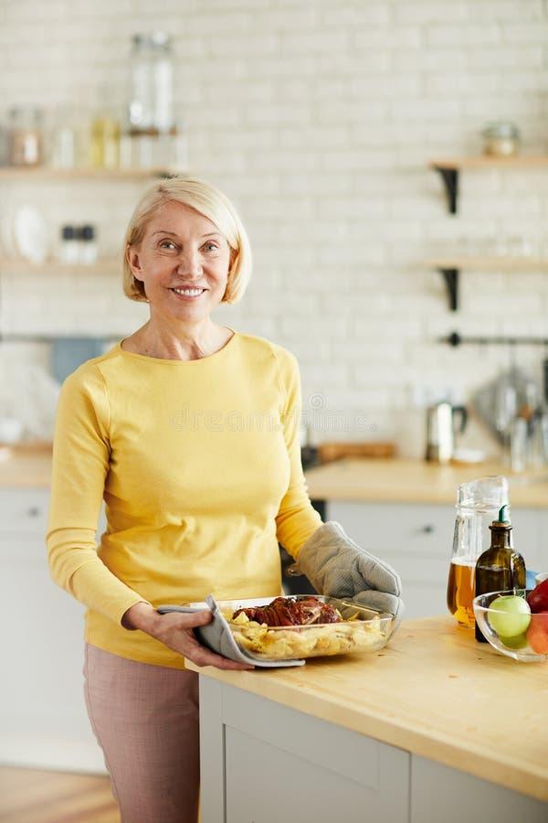 Rijpe vrouw tevreden met haar gekookte schotel stock fotografie
