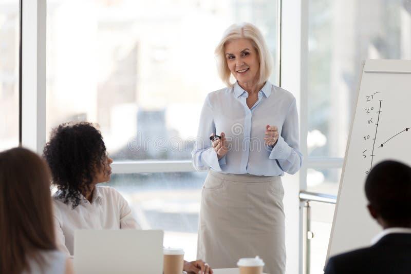 Rijpe vrouwelijke bedrijfsbus die op teamvergadering spreken die s opleiden royalty-vrije stock foto