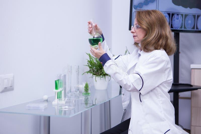 Rijpe vrouwelijke bioloog die een groene oplossing in haar onderzoeklaboratorium bekijken royalty-vrije stock afbeelding