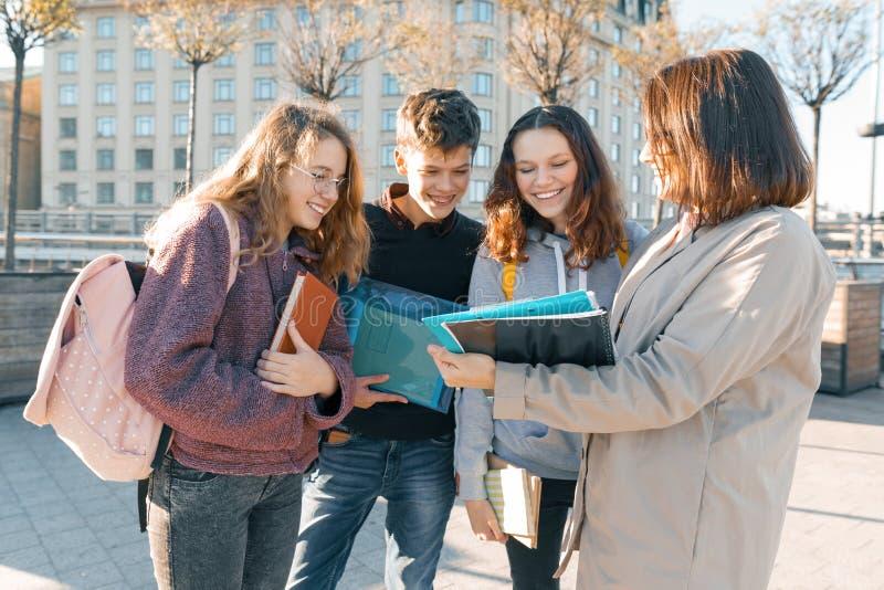 Rijpe vrouwelijke leraar die aan tienerstudenten buiten school, gouden uur spreken stock foto's