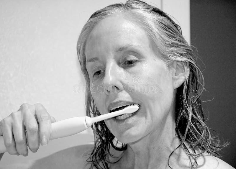 Rijpe vrouwelijke schoonheid die haar tanden borstelen royalty-vrije stock afbeeldingen