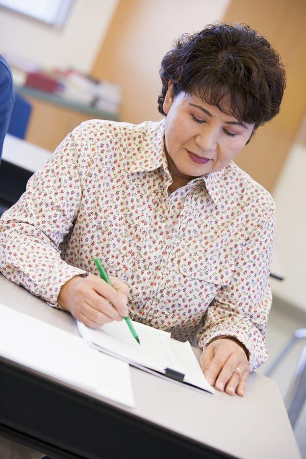 Rijpe vrouwelijke student die in klasse schrijft royalty-vrije stock afbeeldingen