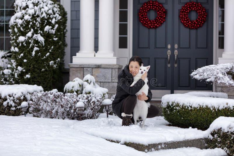 Rijpe vrouwen en haar familiehond buiten in de sneeuw royalty-vrije stock afbeelding