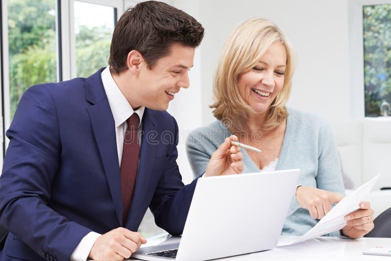 Rijpe Vrouwenvergadering met Financiële Adviseur thuis royalty-vrije stock foto