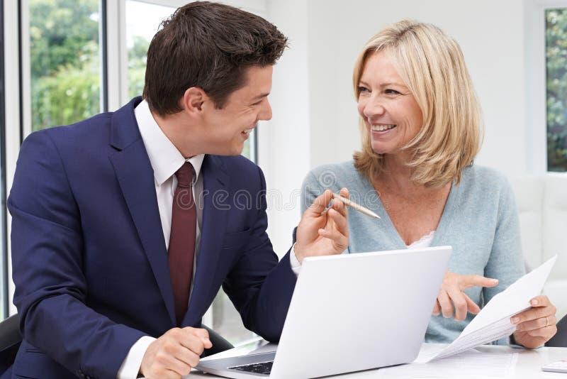Rijpe Vrouwenvergadering met Financiële Adviseur thuis royalty-vrije stock fotografie