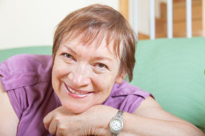 Rijpe vrouwenzitting op bank en het glimlachen stock fotografie