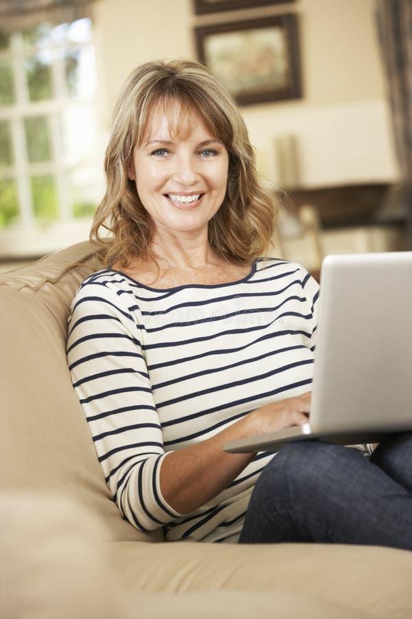 Rijpe Vrouwenzitting op Sofa At Home Using Laptop royalty-vrije stock afbeeldingen