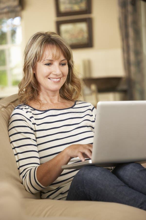 Rijpe Vrouwenzitting op Sofa At Home Using Laptop royalty-vrije stock foto's