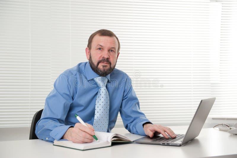 Rijpe zakenman die aan zijn laptop werken royalty-vrije stock foto