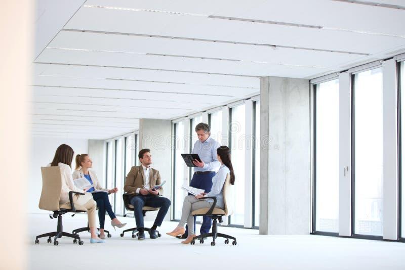 Rijpe zakenman die bespreking met team over stoel in nieuw bureau hebben royalty-vrije stock foto's